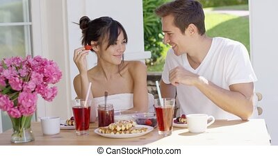 Couple feeding each other at breakfast - Fun loving young...