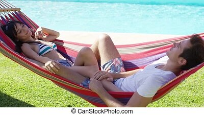 Young couple relaxing in a hammock alongside a swimming pool...