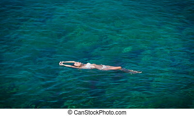Young woman swimming in beautiful azure sea - The slender...