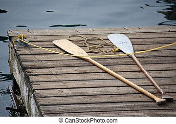 Oars on dock - Two oars on wooden dock at lake.