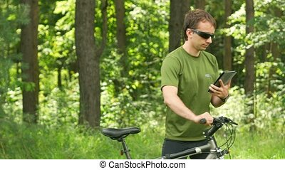 Handsome middle-age man cyclist in gren t-shirt sitting touch a tablet. He is smiling,summer forest on the background. Close-up