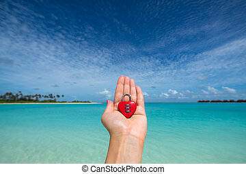 Red heart with a lock on tropical beach in the womans hand