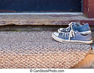 Worn blue tennis shoes on doormat - Pair of old tied blue...