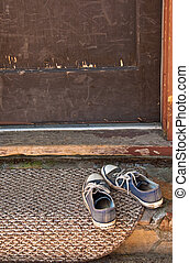 Old blue tennis shoes on doormat - Pair of old tied blue...