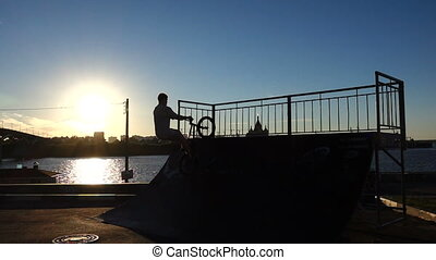 BMX biker. Trick on skate park. Silhouette against a decline