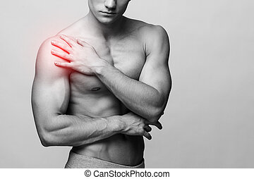 Man with pain problems - Studio shot of a young muscular man...