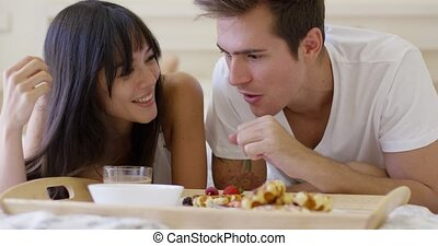 Couple having fruit and waffle breakfast in bed