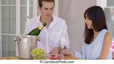 Smiling young couple pouring champagne to drink - Smiling...