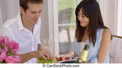 Couple sipping wine and eating fruit - Close up of...