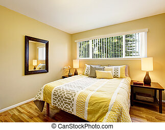 Bedroom interior in yellow tones with hardwood floor.