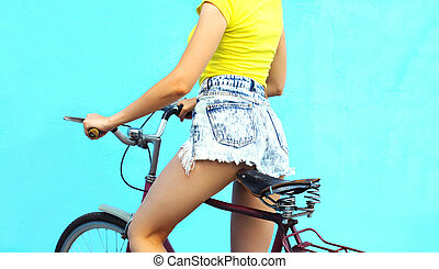 Fashion pretty woman in jeans shorts on bicycle over...
