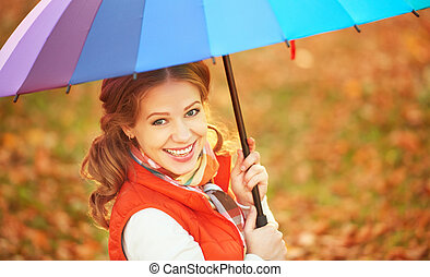 happy woman with rainbow multicolored umbrella under rain in...