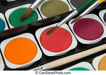palette of multicolor watercolor paints with paint brushes