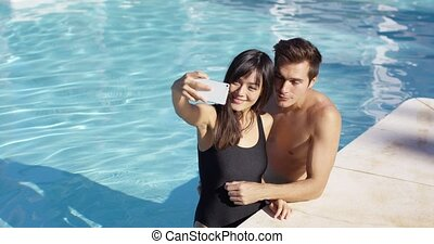 Handsome couple take photo while standing in pool and smile...