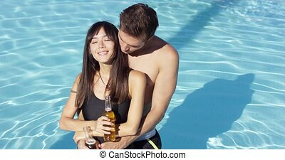 Young beautiful mixed race couple in the pool - Young...