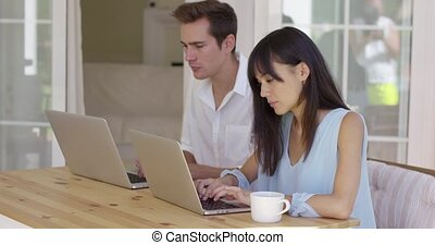 Calm young couple sitting at table using laptop - Calm young...