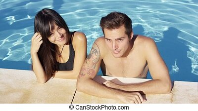 Smiling couple standing in clear pool wave at camera on a...