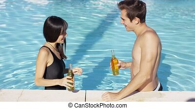Handsome young couple toasts in swimming pool with bottled...