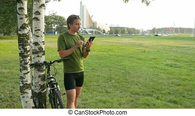 A young man cyclist touch tablet near the birch . Against the background of green field and automobiles.