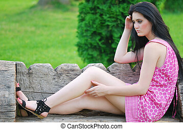 beautiful young lady relaxing on a bench in park