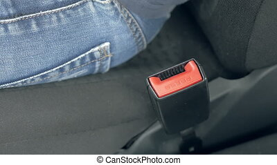 Male hand fastening car safety seat belt - Close up of male...