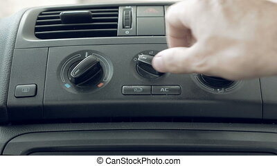 Male hand turning switch of car air conditioner - Close up...