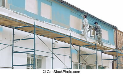 Workers painting by paintbrush building wall - Professional...