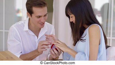 Man fitting ring on finger of girlfriend as he proposes a...