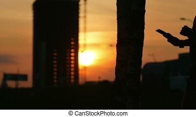 Silhouette of a tablet and hands at sunset. The sun breaks through the construction of a skyscraper