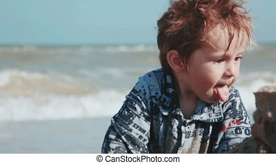 Boy age 2 years old, beautiful appearance, playing in the sand on the seashore.