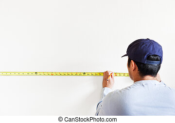 Home improvement - A shot of a man using measurement tape...