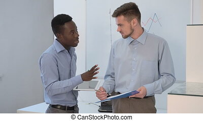 businessman talking in office - two young businessman...