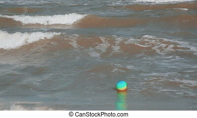 a childs lost beachball drifts offshore - Childrens ball in...