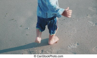 the boy's legs, which runs along the seashore