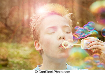 Young boy blowing soap bubbles outdoors in a garden or...