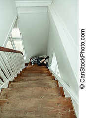 Motionless injured boy lying on the stairs - View from the...