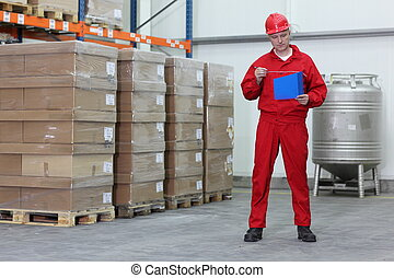 Worker in a company warehouse - Worker reading files in a...