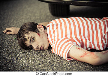 Unconscious boy with eyes open and scratched arm