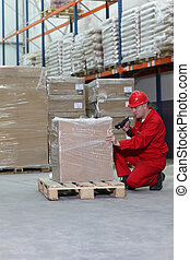 Worker with bar code reader working - Worker in red uniform...