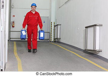 Factory worker carrying bottles of - Factory worker in red...