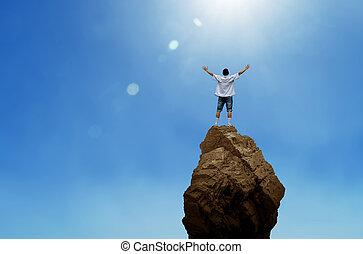 Cheering man open arms on mountain peak cliff - Man on top...