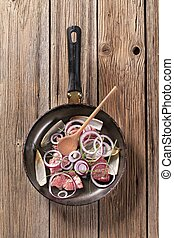 Pan frying meat and onion - Pieces of meat and onion on...