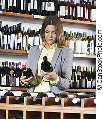 Mid Adult Woman Choosing Wine Bottles - Portrait of mid...