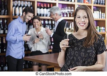 Happy Woman Holding Wineglass With Friends In Background