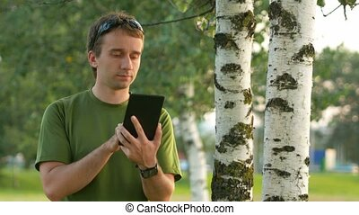 A young man cyclist touch tablet near the birch . Against the background of green field and automobiles