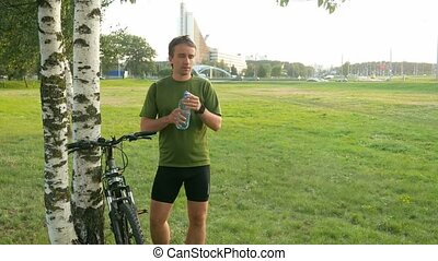 A young man cyclist stops and drink water from bottle. Against the background of green field and automobiles