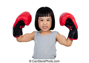 Chinese little girl wearing boxing glove showing power in...