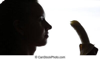 Close-up of Young amazed woman holding a banana, she is...