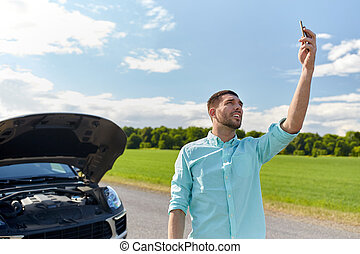 man with smartphone and broken car at countryside - road...
