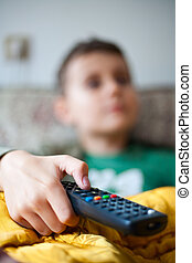 Holding tv remote control - Child watching tv, holding...